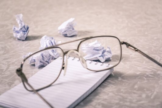 Glasses sitting on a notepad with wads of crumpled up paper scattered as worker struggles with feeling off