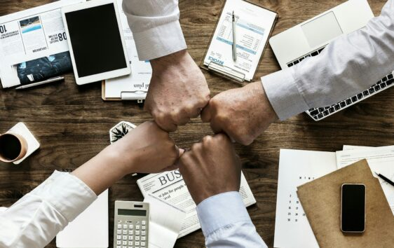 Four team members fist bumping to boost morale in the office above a table filled with papers and technology