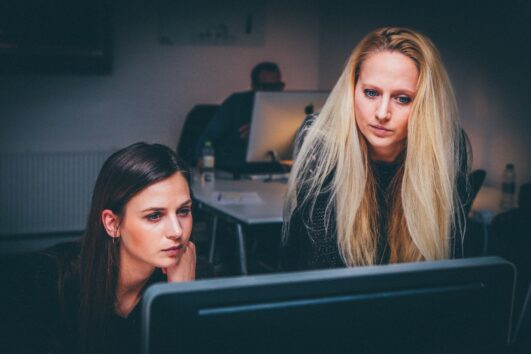 Woman helping to boost morale of her teammate by working at a computer screen while a man works at a computer in the background